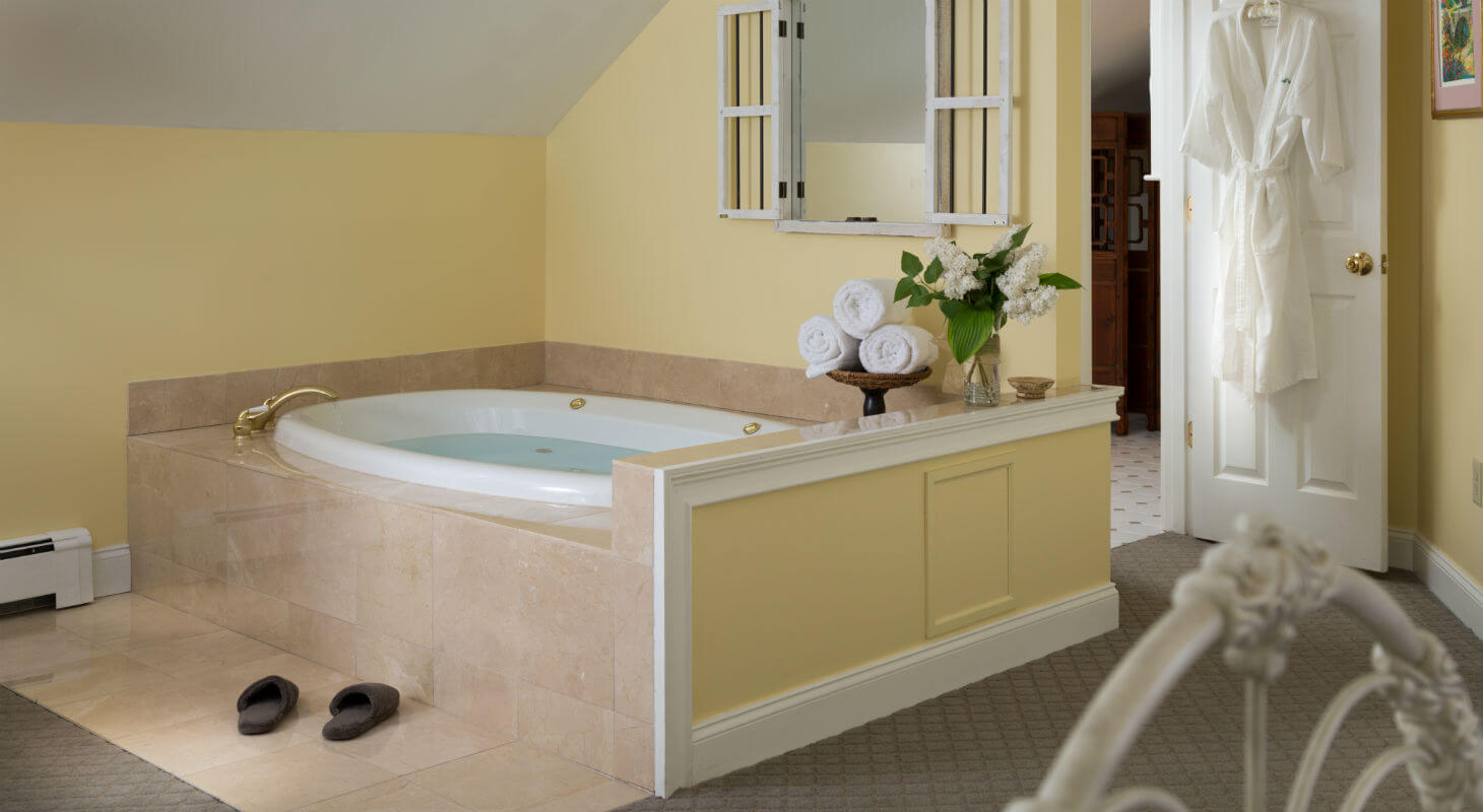 Granite Whirlpool tub filled with warm water by slippers