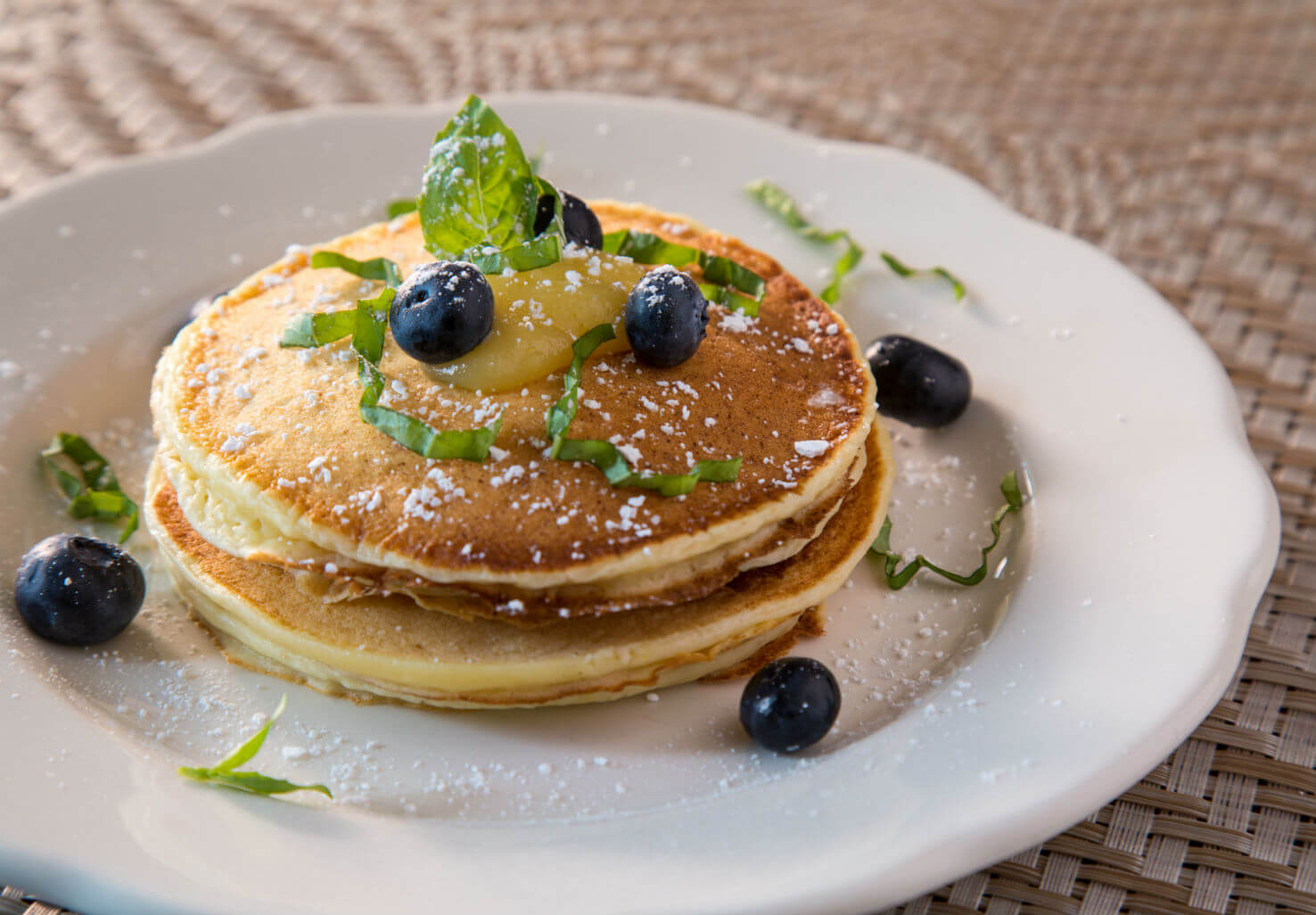 Plate of fresh pancakes with powdered sugar, herbs and blueberries