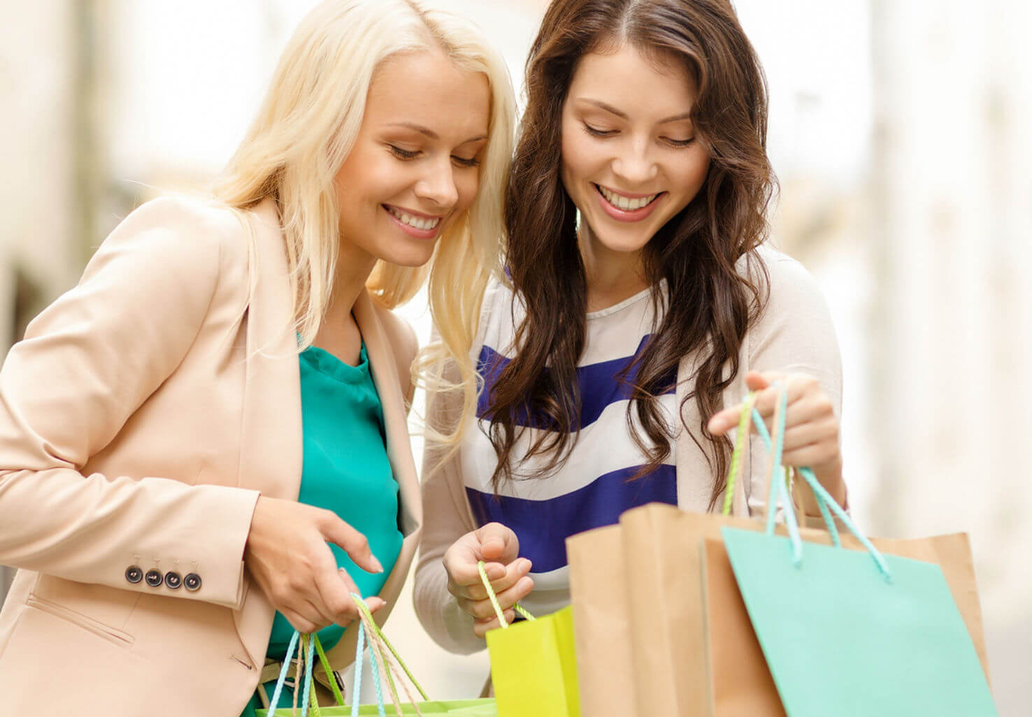 Two women happily looking at their shopping bags