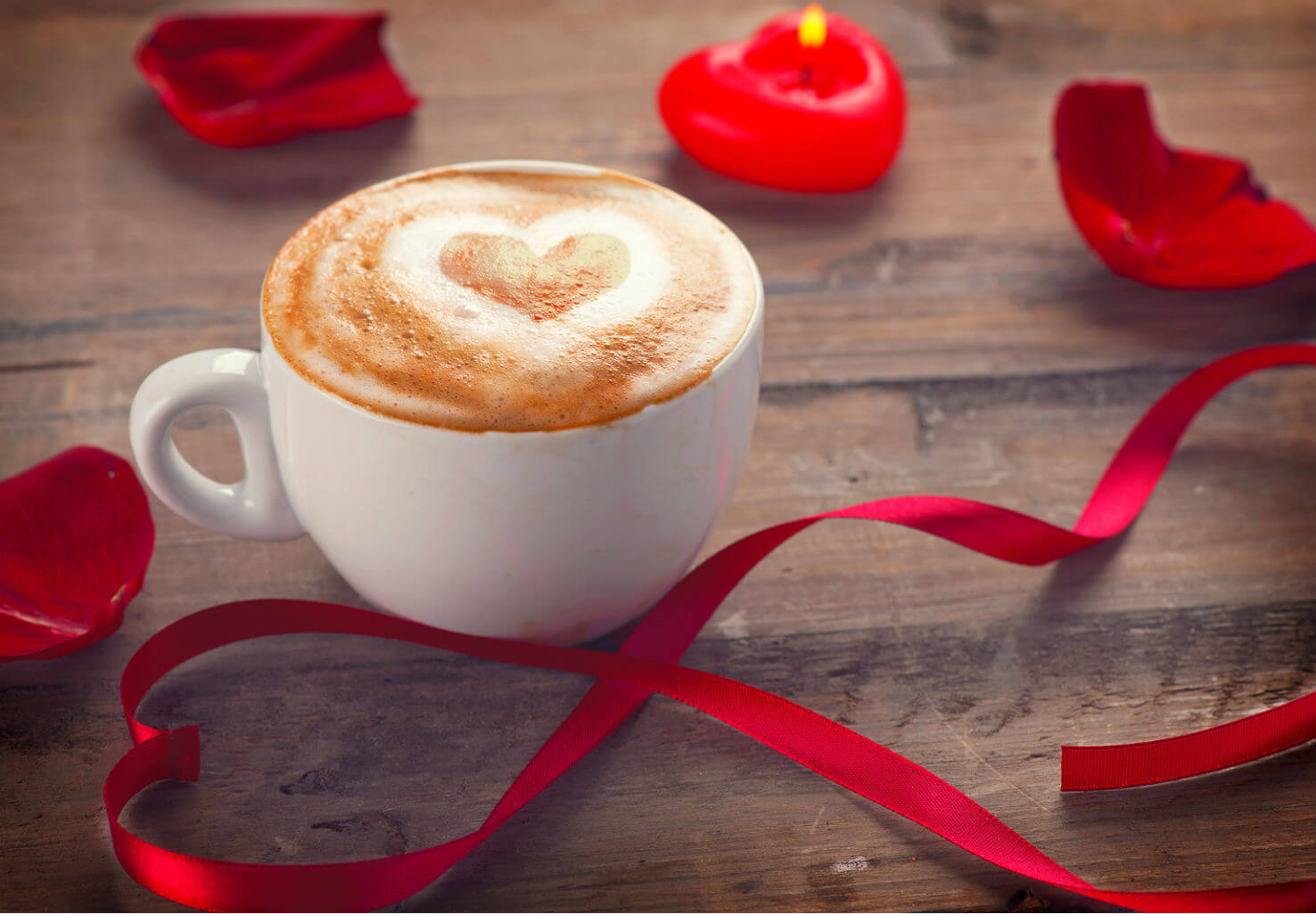 Hot chocolate cup with heart pattern sits on table by ribbon, rose petals, and heart-shaped candle