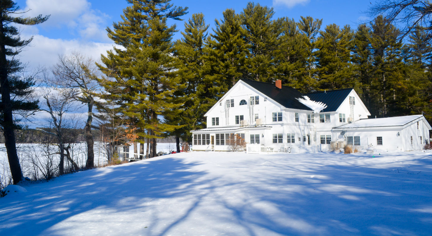 Exterior of the Wolf Cove Inn covered in snow