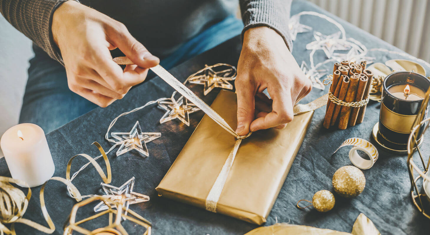Person lovingly wrapping a Christmas gift