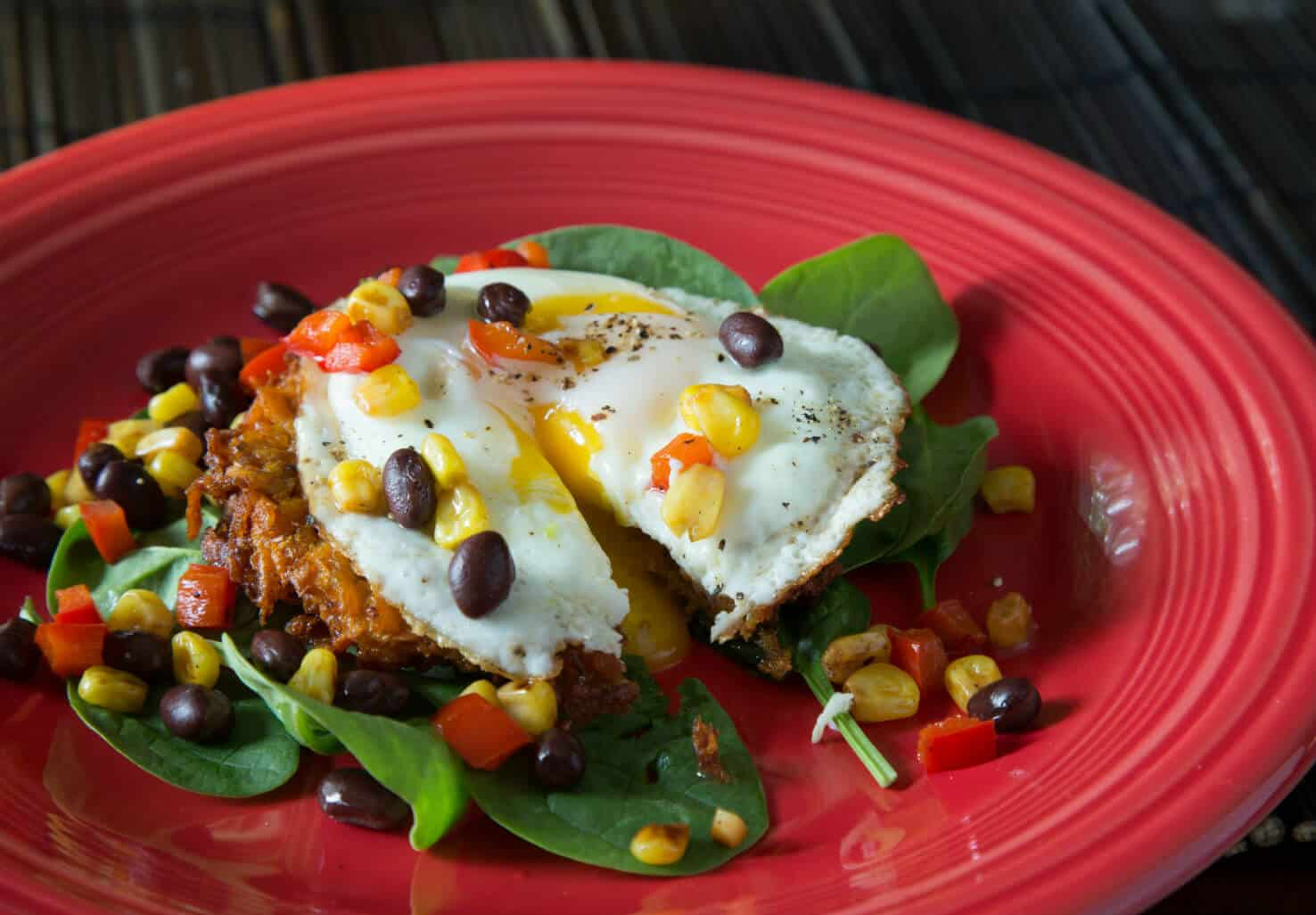 Savory breakfast with fried egg over hash browns and baby spinach