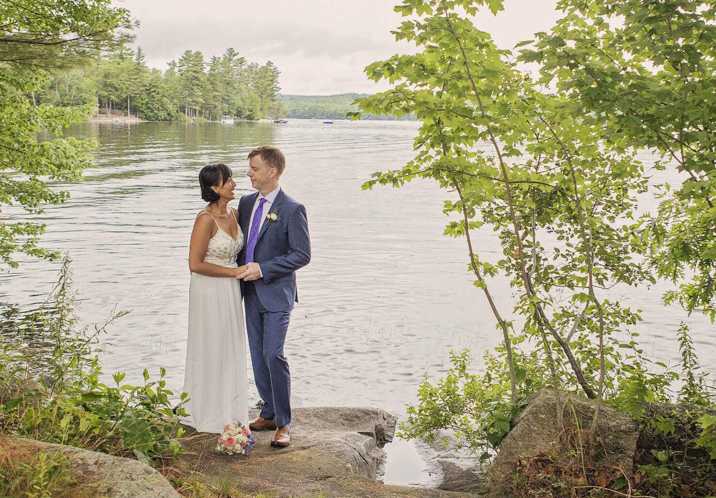 Newlyweds standing by lake