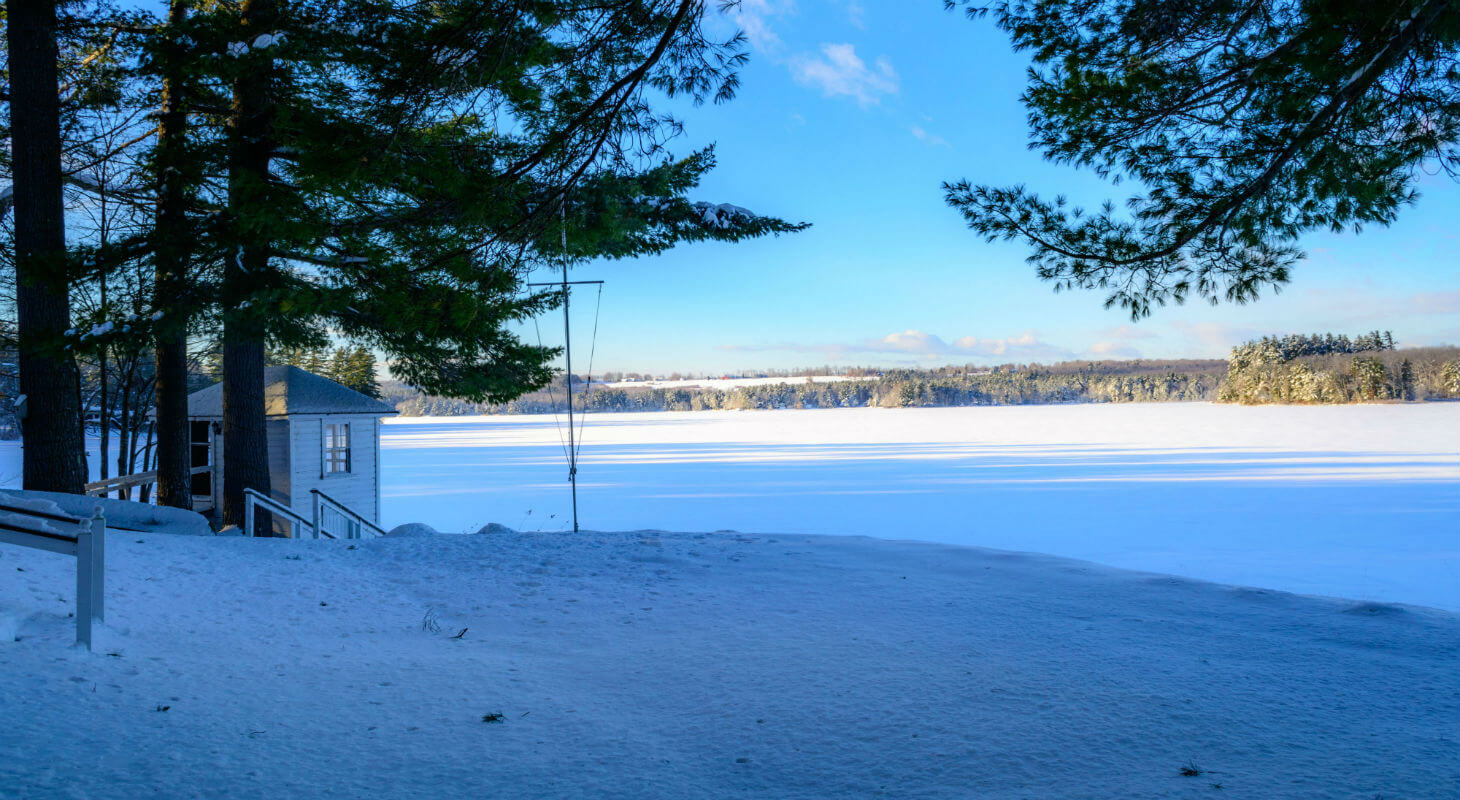 Snowy field and Tripp Lake outside of the Wolf Cove Inn