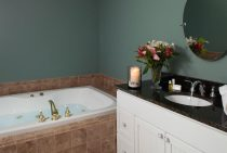 Jetted spa tub next to sink with flowers and candle