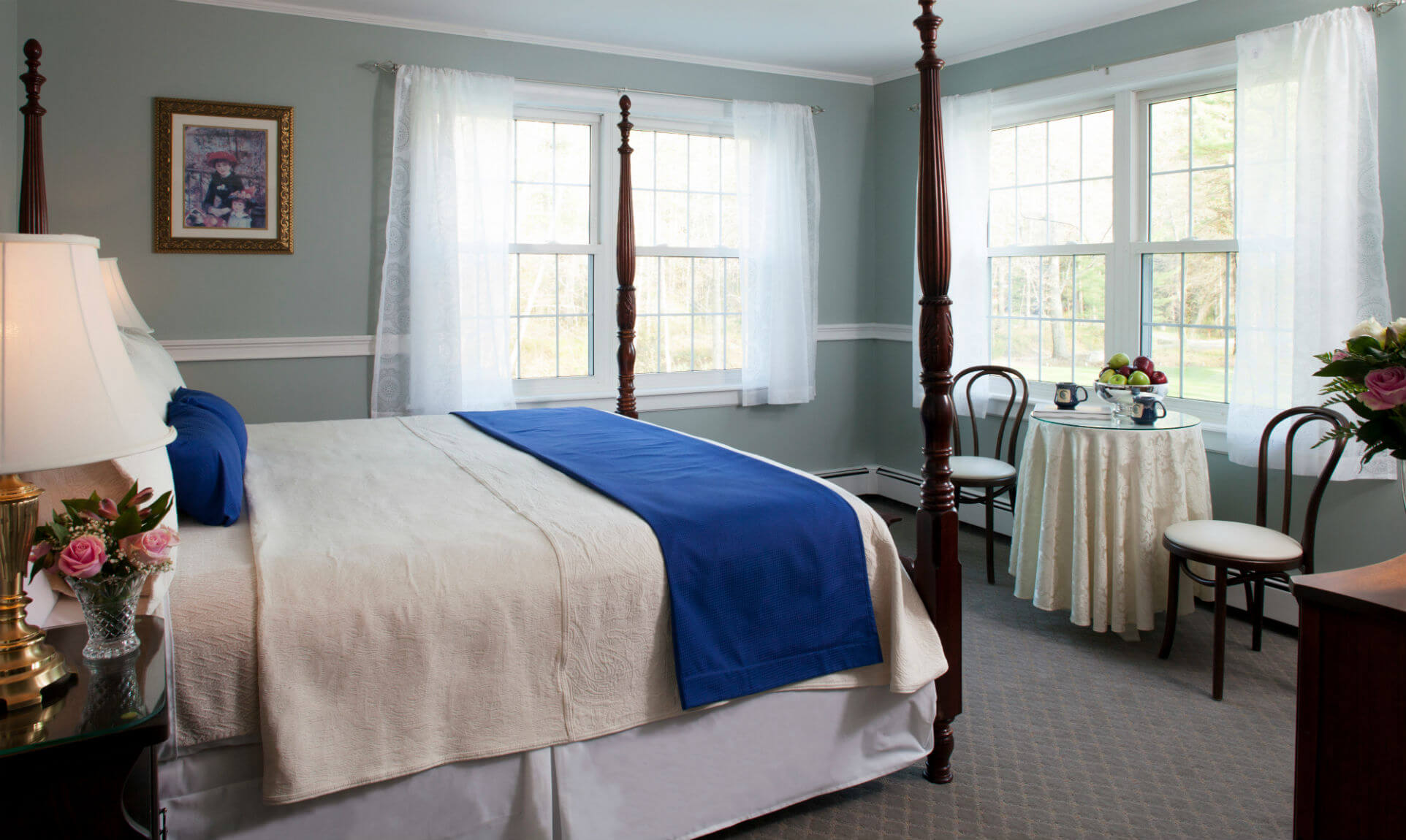 Soft bed with white comforter near sitting area with antique chairs
