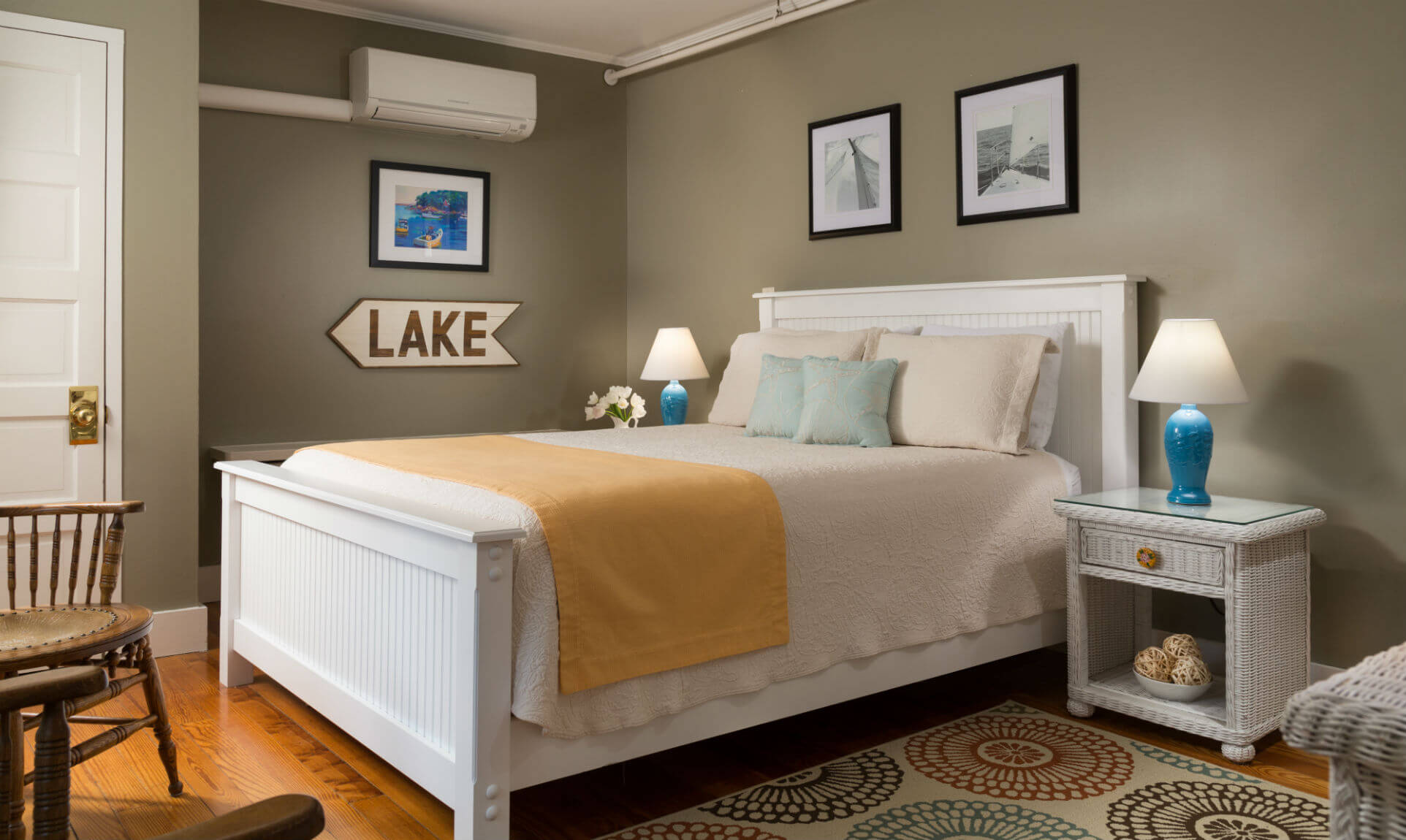 Comfortable bed next to lake sign and floral rug