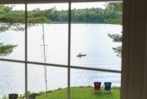 Window overlook into lake with canoer floating across it