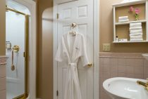 Soft bathrobe next to shower and sink in the Penobscot Bay room