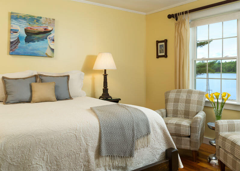 Soft bed next to sitting area and window in the Penobscot Bay room