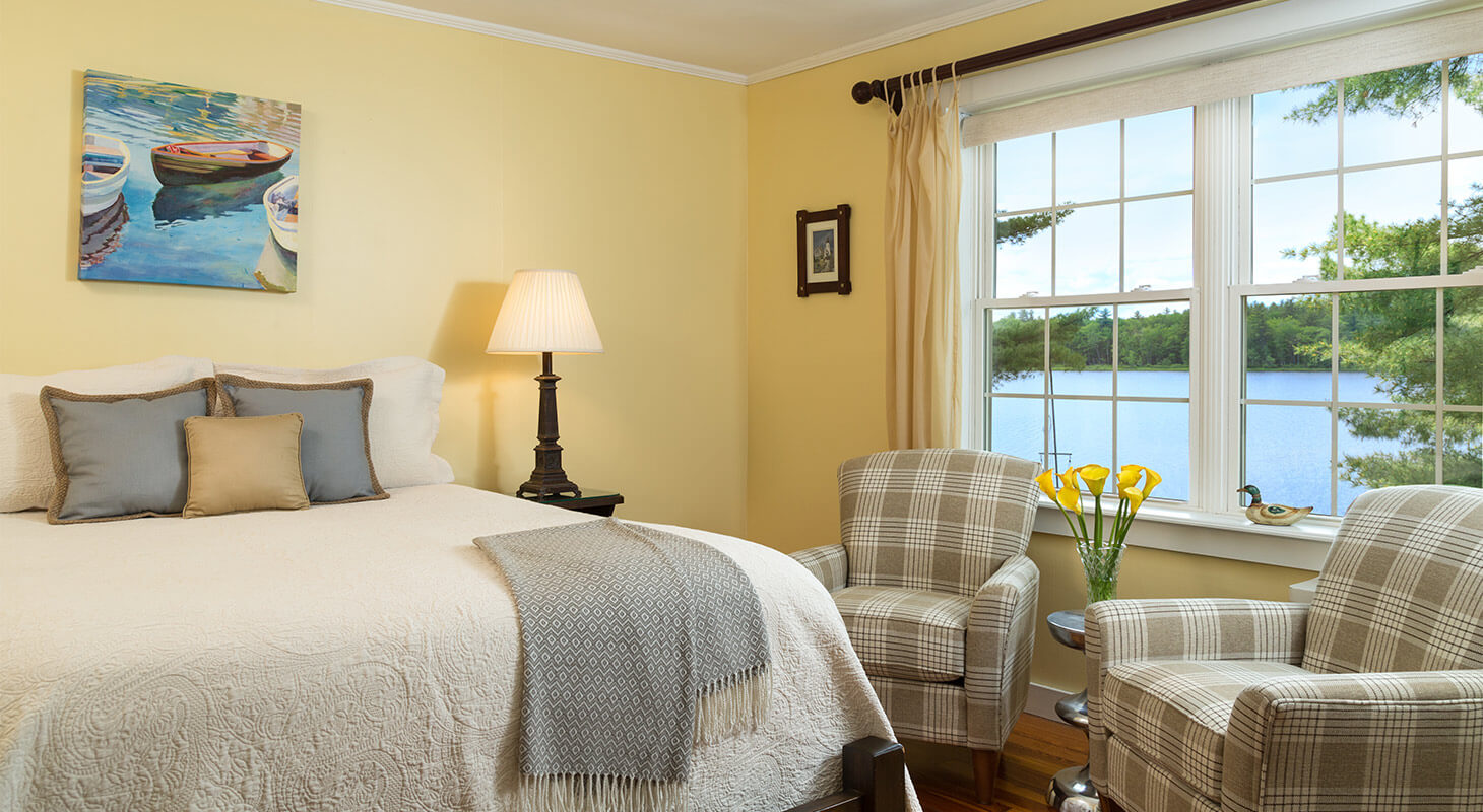 Soft bed next to sitting area with vase full of bright flowers and window
