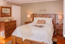 Comfortable white bed in room with dark wood furnishings and painting