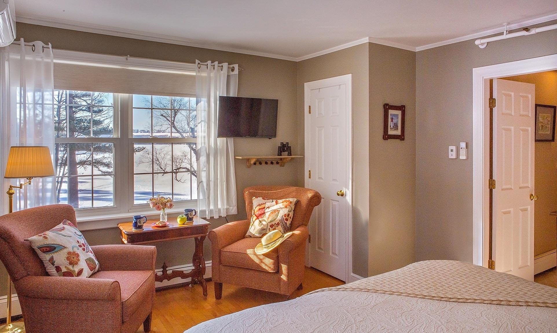 Comfortable white bed across from two plush sitting chairs and window
