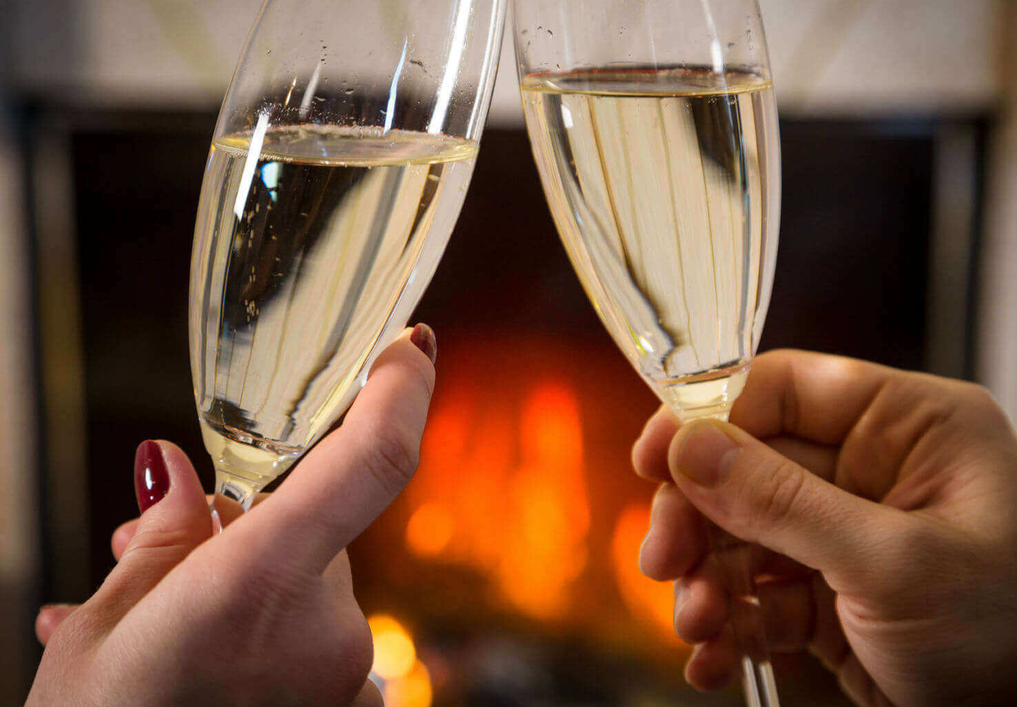 Two people toasting with champagne glasses in front of fireplace