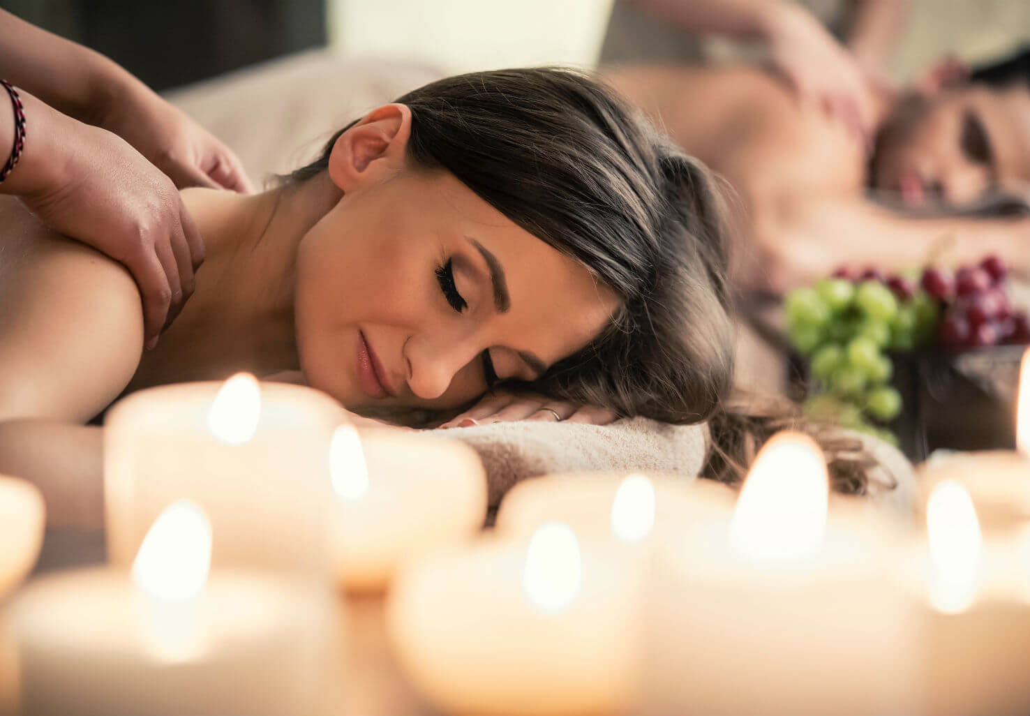 Woman receives massage while lying near candles