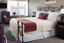 Soft buttercream-colored bed with maroon blanket and pillows next to large window