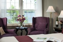 Maroon chairs next to vase and lamp in sitting area next to bed