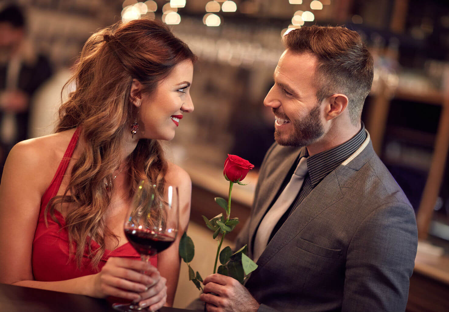 Man presents woman with rose while she holds wine