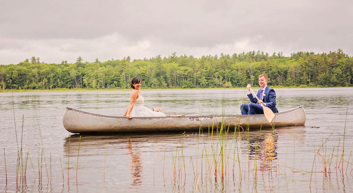 Bride and groom paddle a long canoe across lake