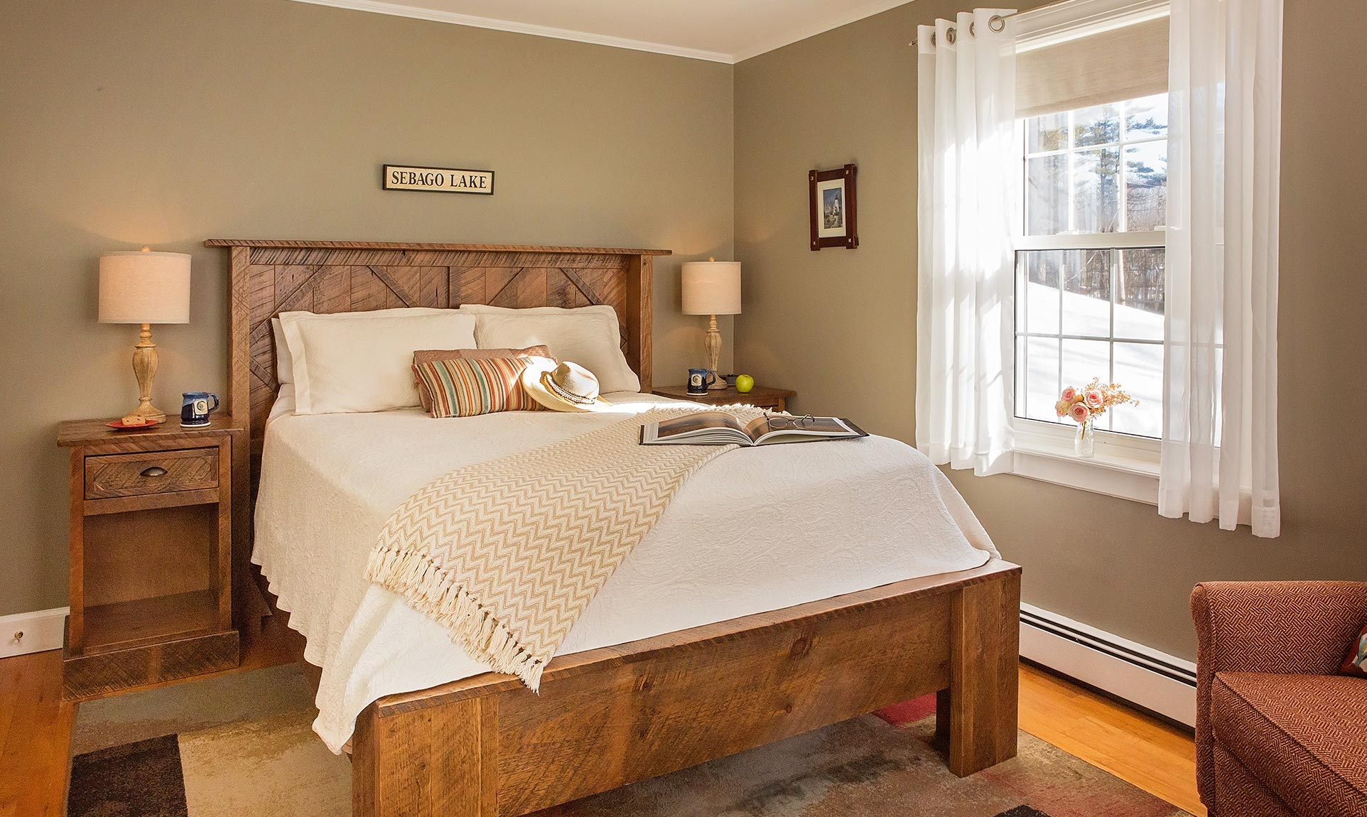 Relaxing white bed with wooden backboard under Sebago Lake sign