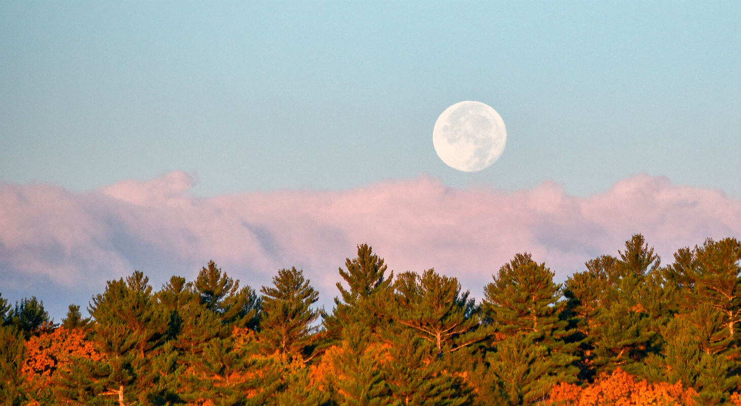Moon setting past clouds over fall foliage