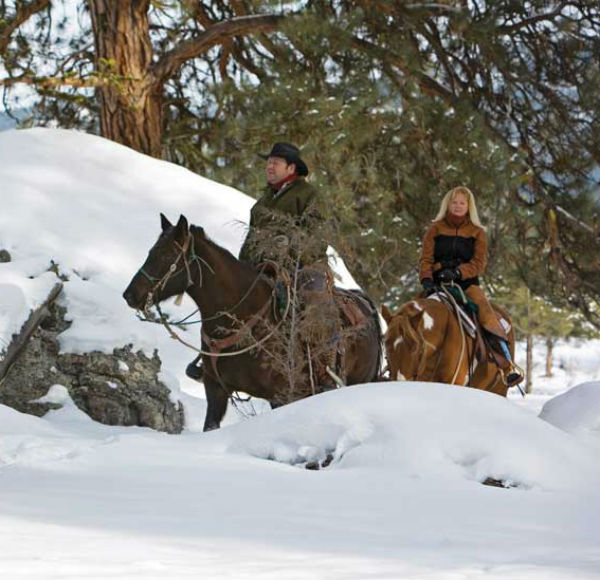 Couple riding horses through the snow
