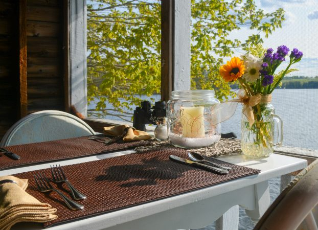Open placemats for two at the Boathouse Bistro, with fork, knives, spoon, and vase of fresh flowers