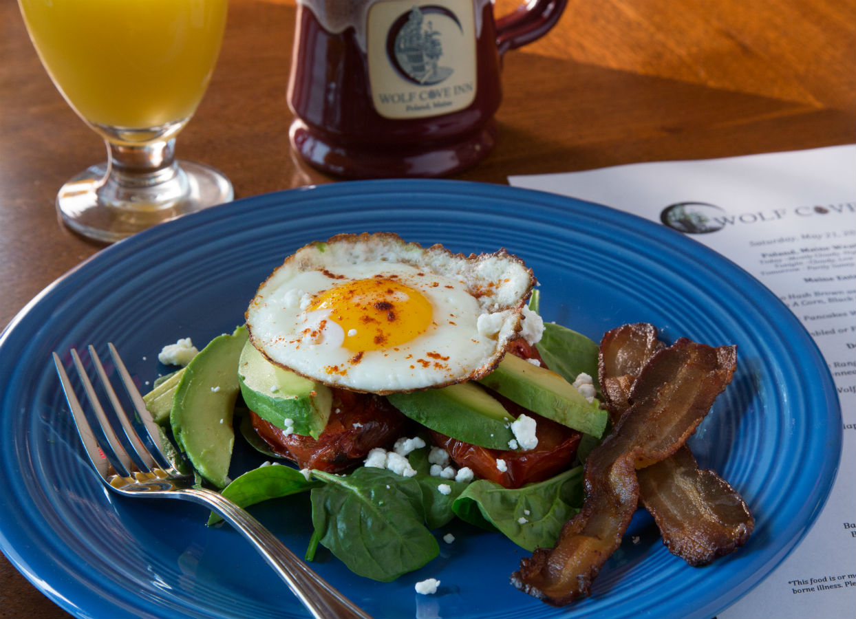 Sunny side up egg over avocado and fresh basil with crisp bacon on the side.