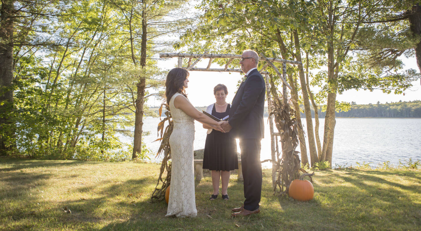 Bride and groom hold hands in front of arch under birch trees