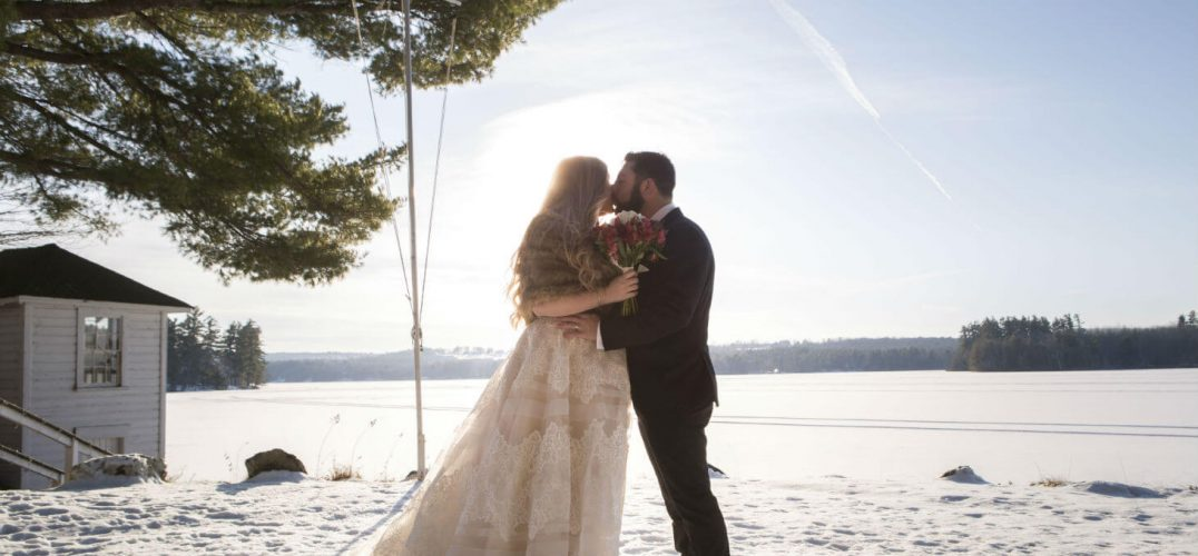 Bride and groom kiss in snow by lake
