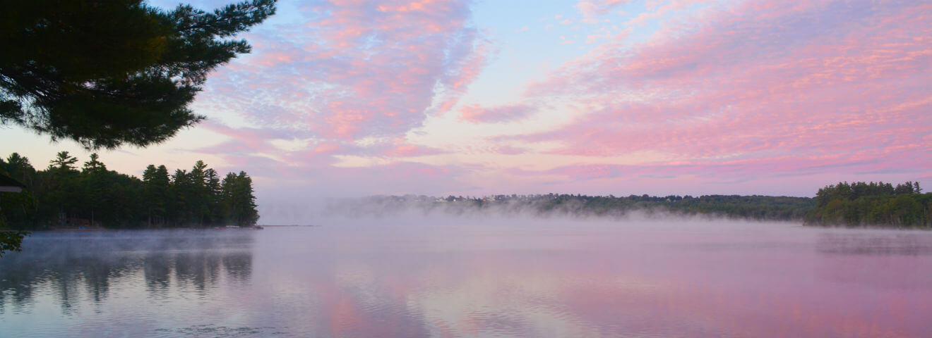 Pink clouds on a blue sky at sunrise over Tripp Lake