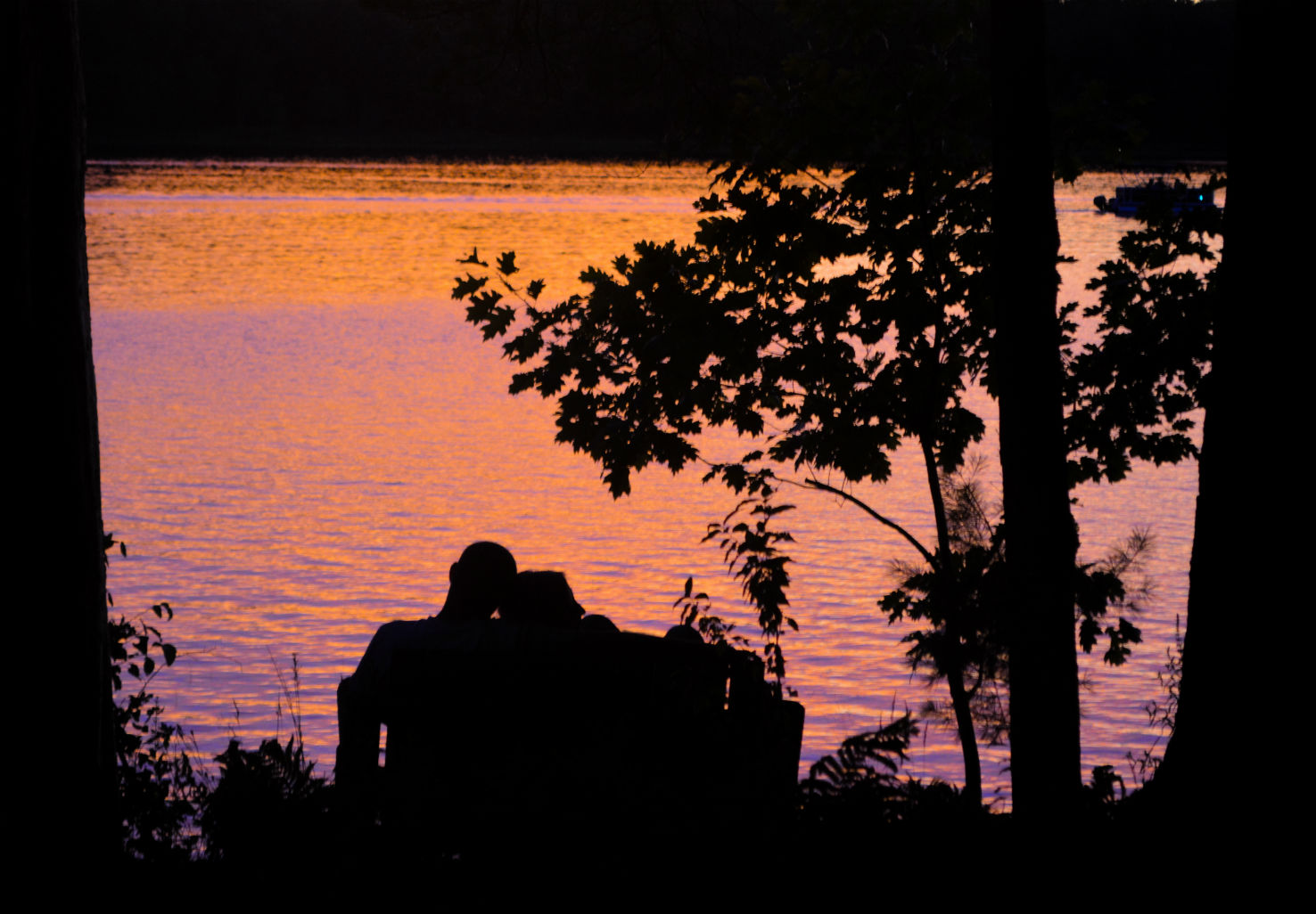 Silhouette of couple leaning heads on each other by lake