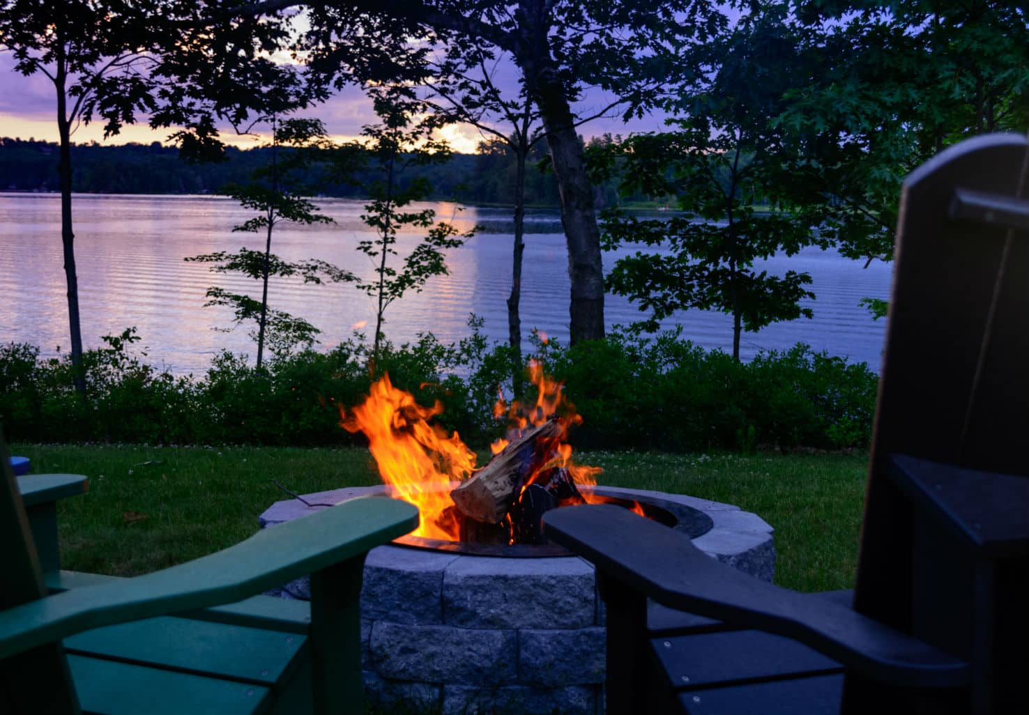 Empty chairs next to firepit overlooking lake