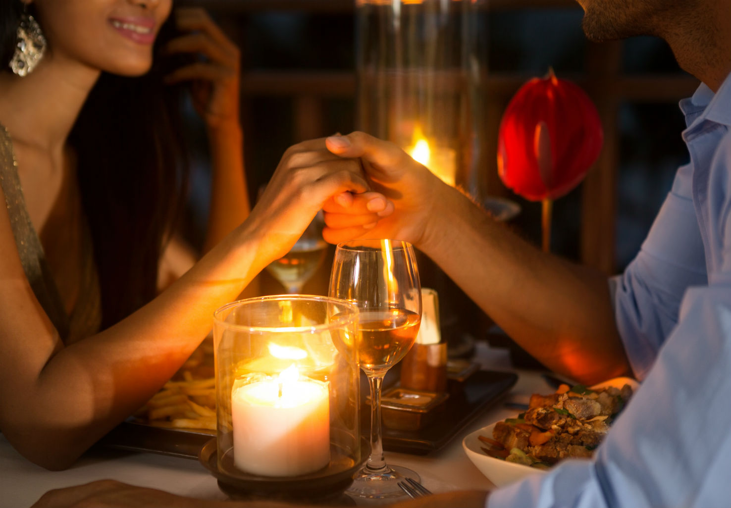 Couple holding hands over romantic candlelit dinner