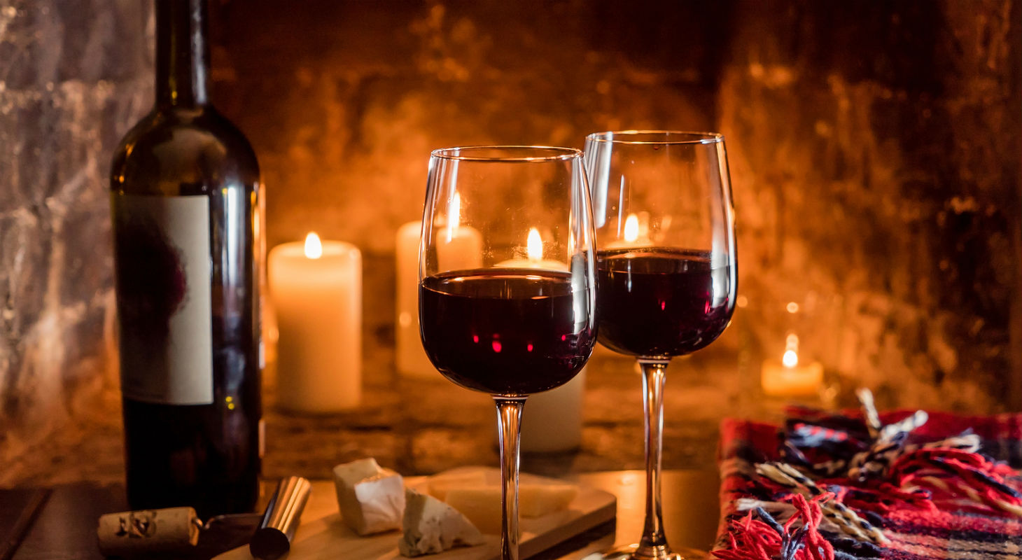 Wine glasses on a table in front of the fire