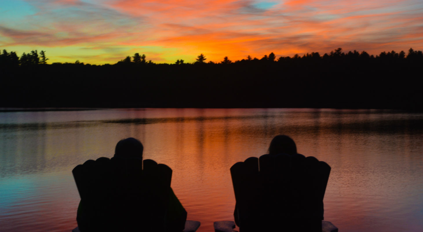 Silhouette of couple watching sunset together across lake
