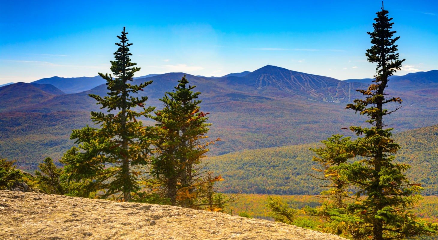 Rocky outlook over a fall Maine forest on Little Bigelow