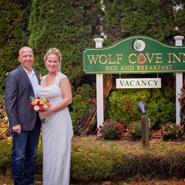 Bride and Groom in front of Wolf Cove Inn Sign