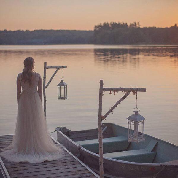Bride on dock overlooking the water at sunset