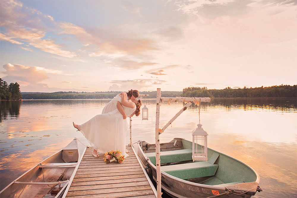 Brides kissing on dock at sunset