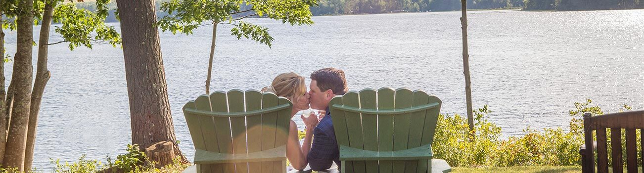 Elopement couple kissing in adirondack chairs