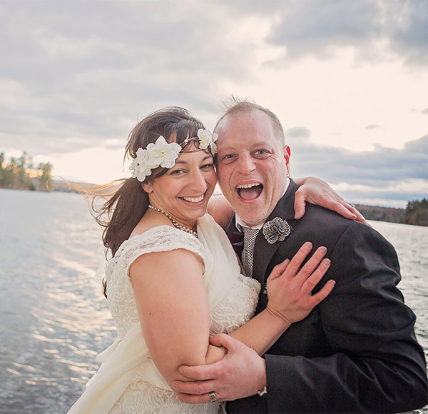 Smiling groom with his bride in front of Tripp Lake