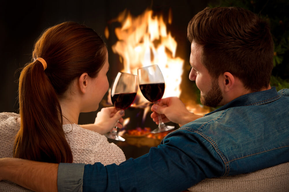 Couple by fireplace with wine