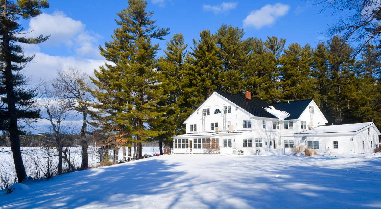 Wolf Cove Inn in a snowy landscape during winter with blues skies and tall pine trees in the background
