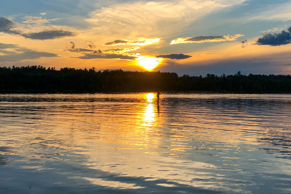 Paddle boarding on Tripp Lake at sunset. This could be you on your Maine Honeymoon.