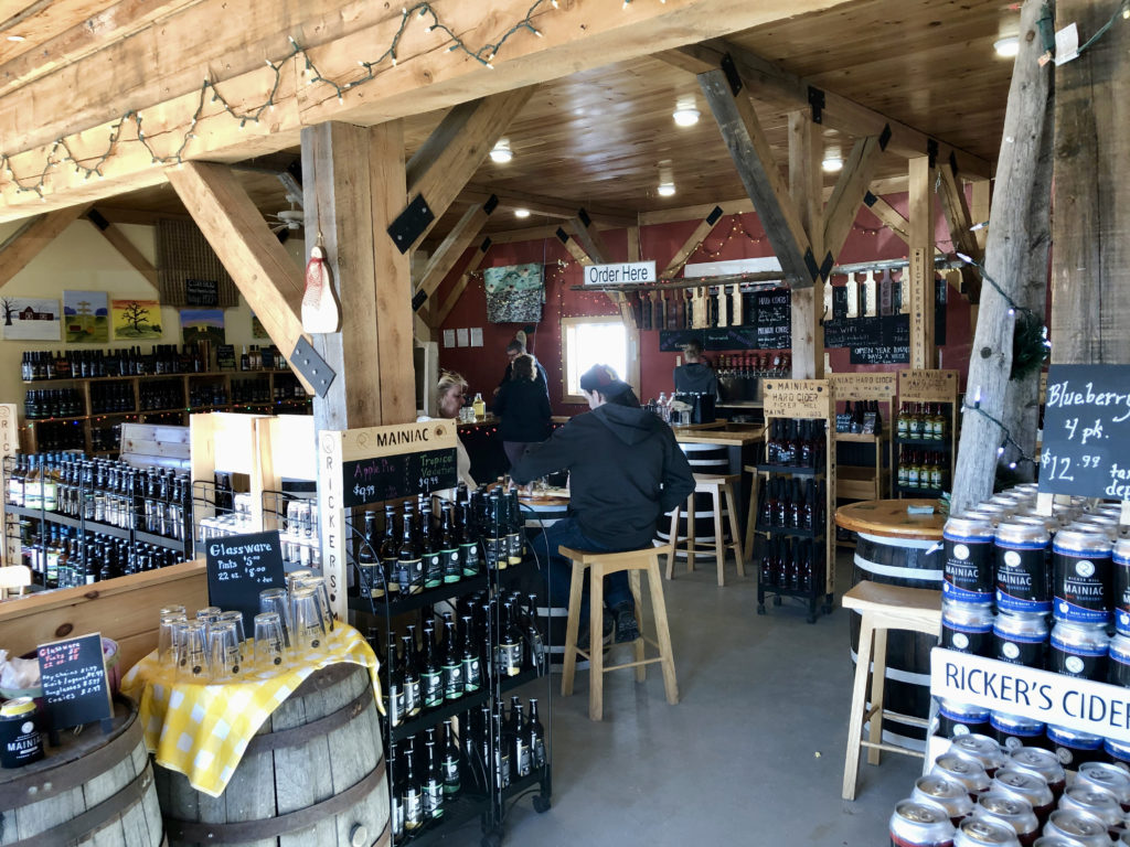 Interior of a tasting room with barrels, bottles, and cans under a wood timbered ceiling