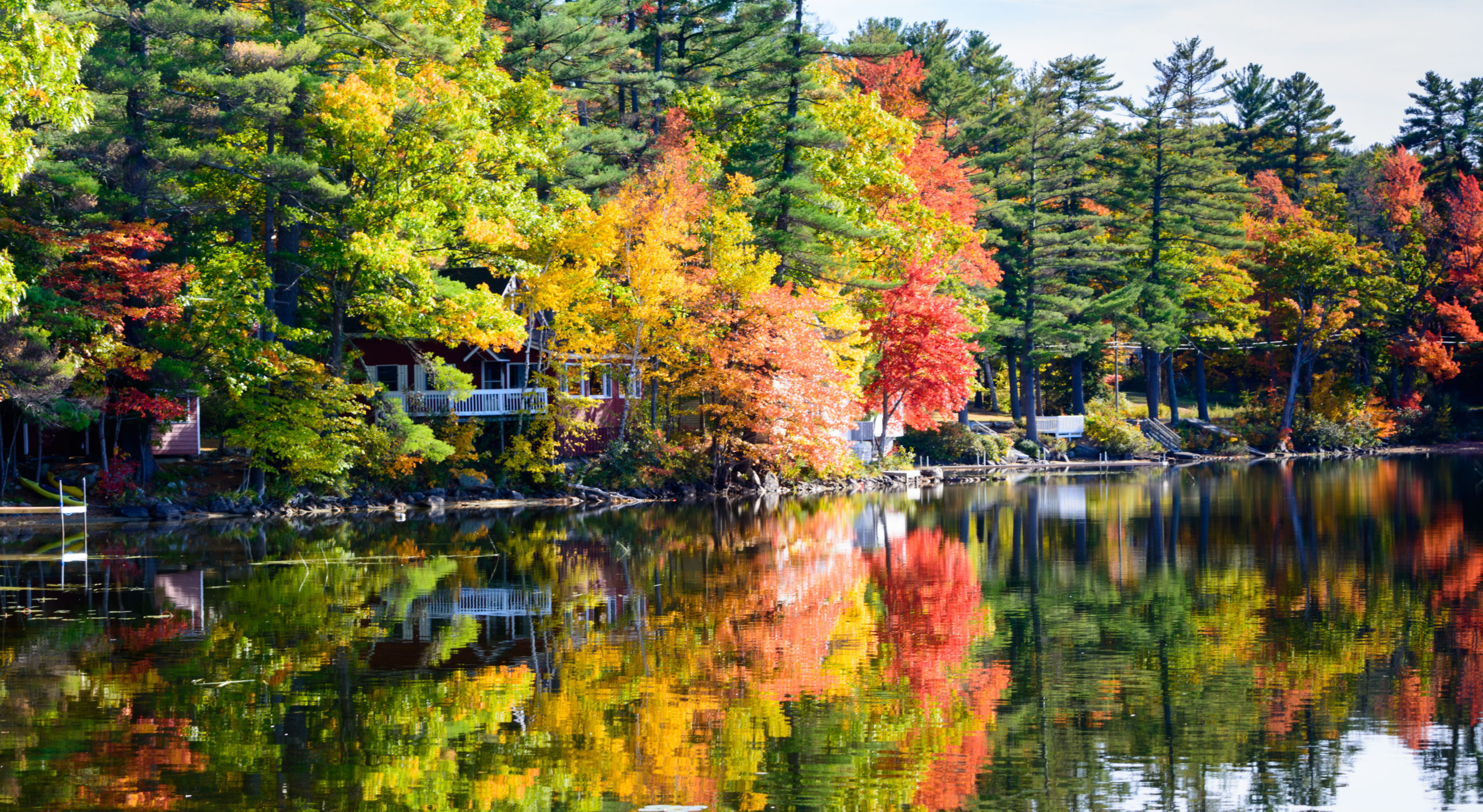 red, yellow, and green foliage reflecting on a lake surface
