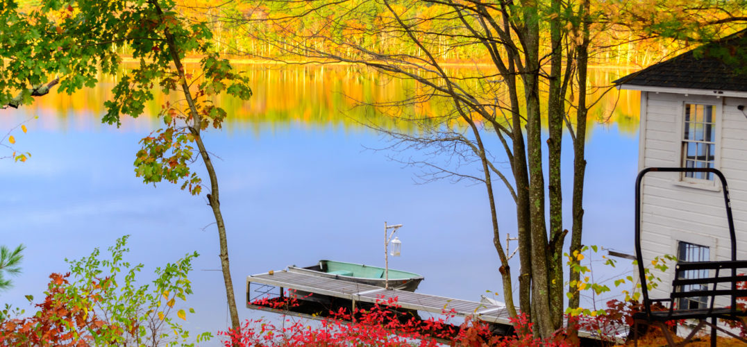 lake surrounded by red, orange, and yellow fall foliage
