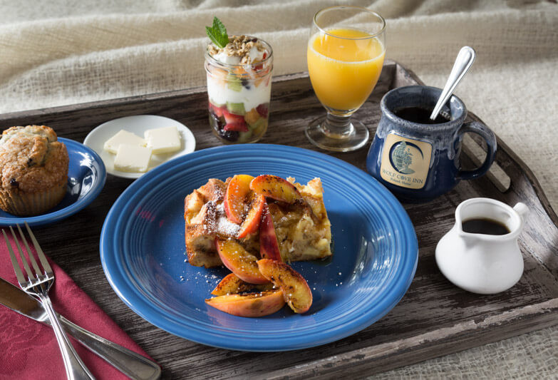 breakfast tray with french toast cover in peaches, coffee, orange juice, fruit parfait, and muffin